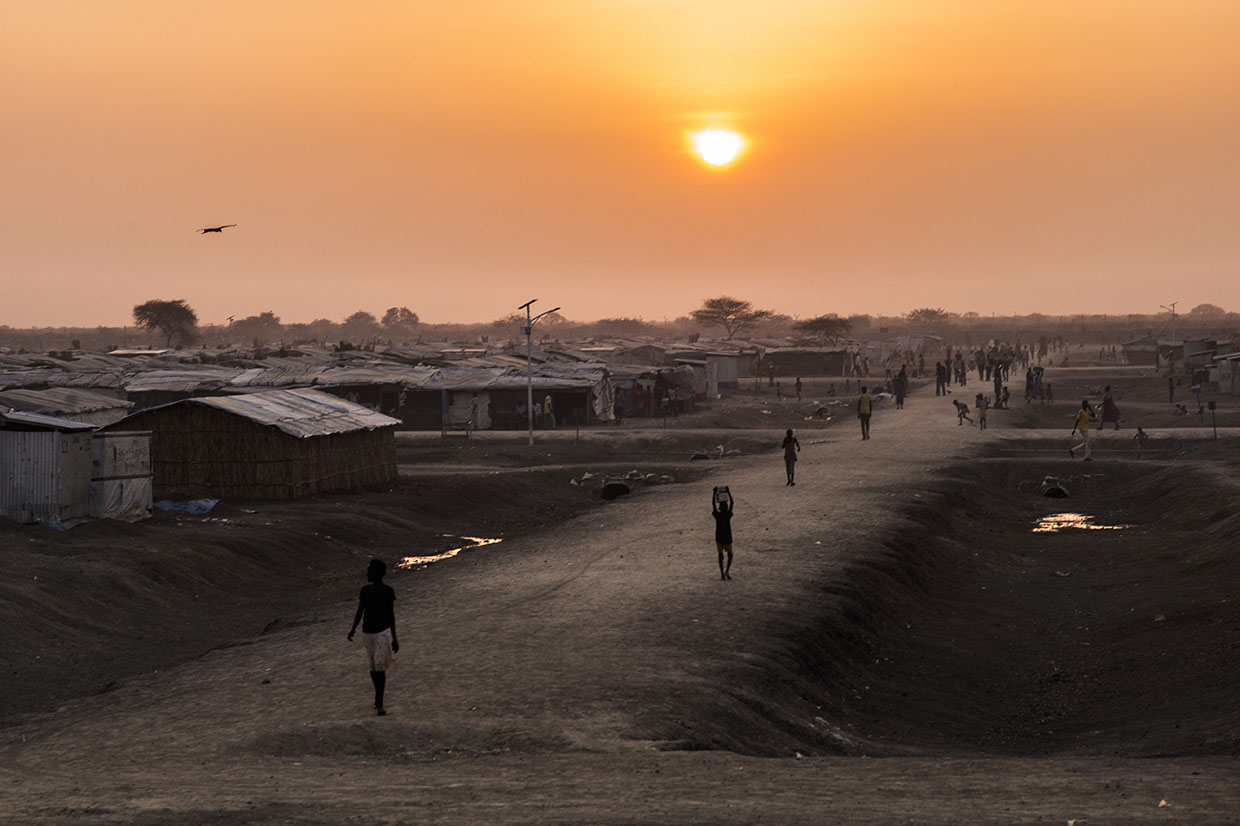 Individuals walking a road through a refugee camp at sunset.