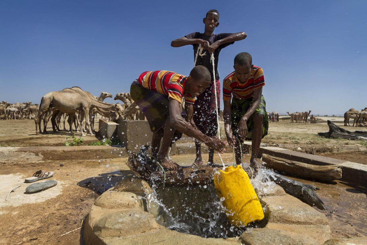 Three young people work together to haul up water in Ethiopia