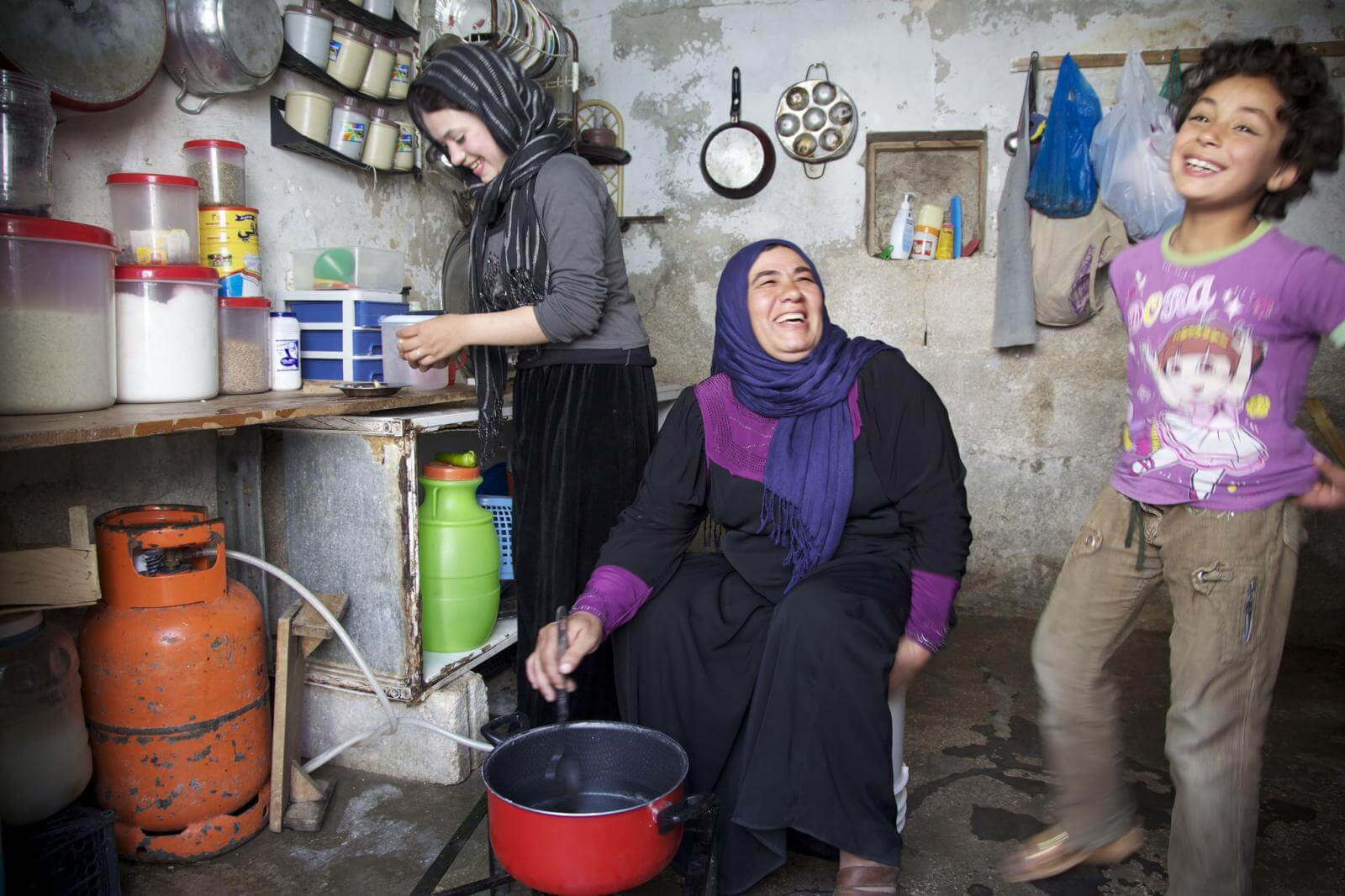 A family laughing and cooking in Jordan