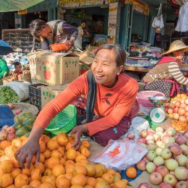 Woman selling fruit at an open air market in myanmar