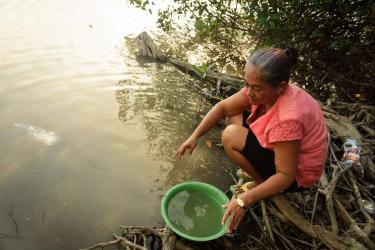 Oriana collecting water into a large green bowl from the river near her makeshift camp under the bridge.