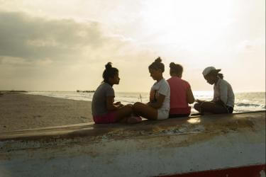 Four youth sitting at the beach with sun behind them