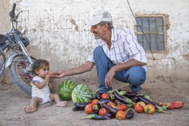 Syrian granddaughter and grandfather eating watermelon