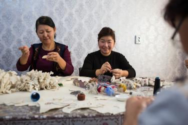Women sitting around a table working on felt handicrafts