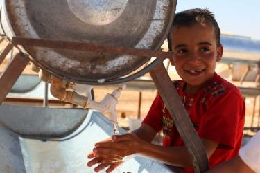 boy washing hands at refugee camp water station