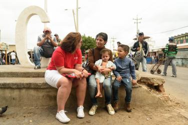 Mercy corps team member speaking to mother and two children in colombia
