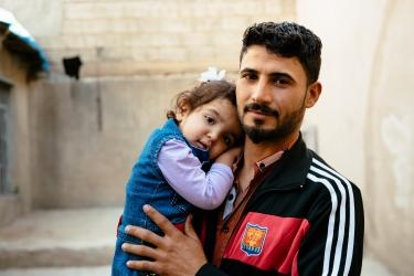 Father holding young daughter in iraq