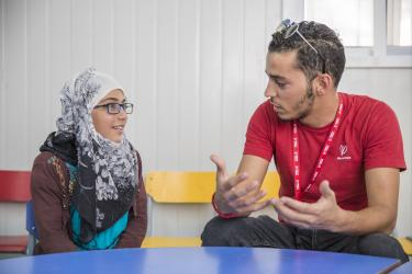 Deputy Program Manager Omar Al-Tal speaks with Amani, 14, at a Mercy Corps safe space inside the Azraq refugee camp in Jordan.