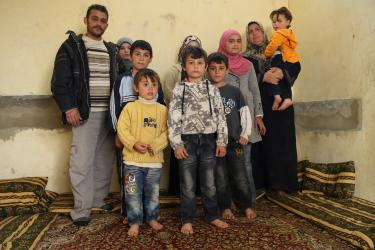 Abid with his wife and eight children in their one-room home.