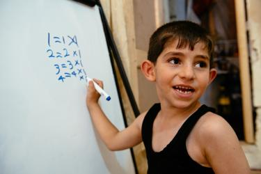 A young boy writing multiplication tables on a dry erase board