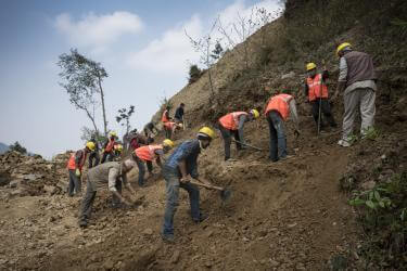 Nepalese road construction crew working on hillside.