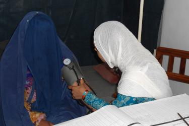 A midwife checks a woman's blood pressure