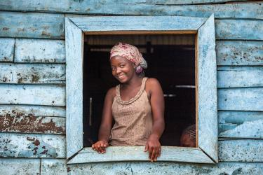 Woman smiling, at her window