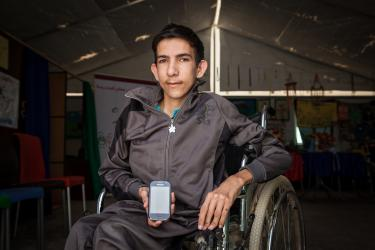 A young man in a wheelchair holds a smartphone