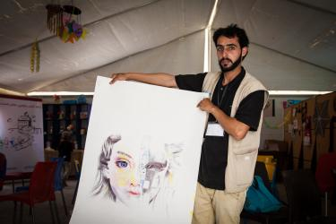 A young man holding a large painting of a girl's face
