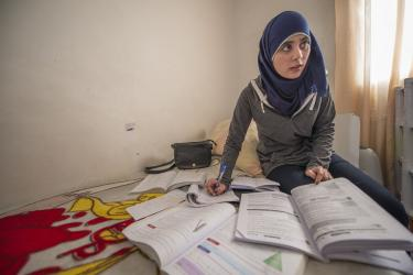 Amina pictured with textbooks and papers