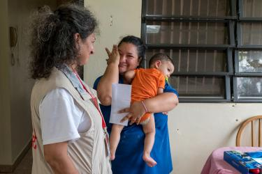 A woman holding a baby wipes away tears and smiles at a mercy corps team member in puerto rico