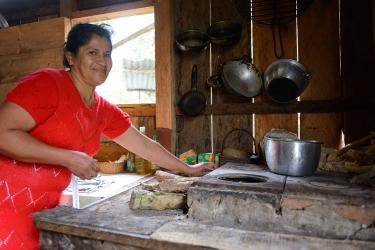 A woman wearing a red dress prepares food in her kitchen in colombia