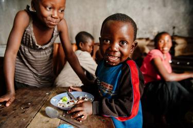 Child eating and smiling in drc