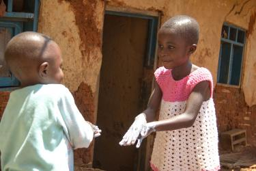 Christine, 6, and her little brother Gabriel, 3, practice their hand washing techniques. Photo: Rudy Nkombo/Mercy Corps