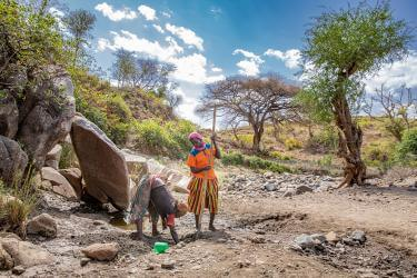 Two women dig in the sandy riverbed to access water during the dry season in ethiopia