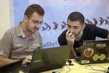 two men working together on laptops