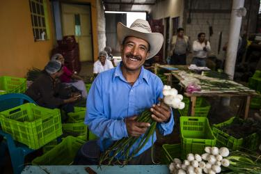 A man holding harvested vegetables in guatemala