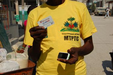man holding mobile phone and cash card