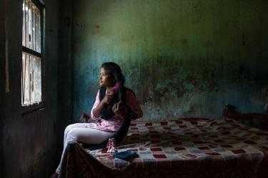 Teen girl in india sitting on her bed and brushing her hair