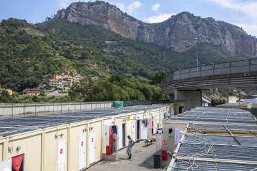 Scene of temporary shelters at port at base of mountain