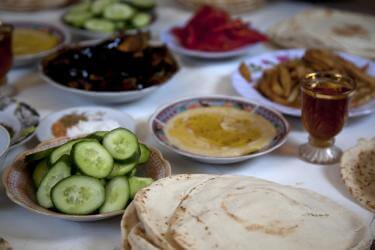 Several small dishes filled with hummus, sliced cucumber and other vegetables, and pita