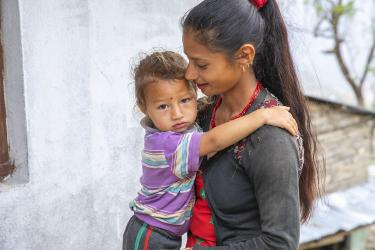 A woman holds a toddler in nepal