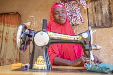 Nigerian woman at sewing machine.