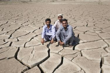 Three pakistani men crouch on dry, cracked earth.