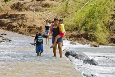 Family crossing a shallow stream on foot