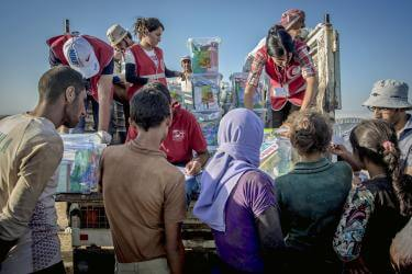 Syria team members handing supplies to people