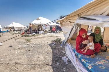 Women and baby under shelter in syria