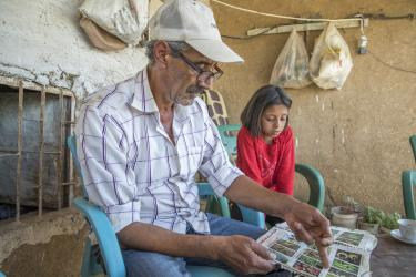 Abu goubran and his daughter sitting side by side, looking at a seed catalog