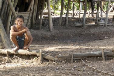 A boy squatting and smiling in timor-leste