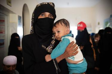 A woman holding her infant son in yemen