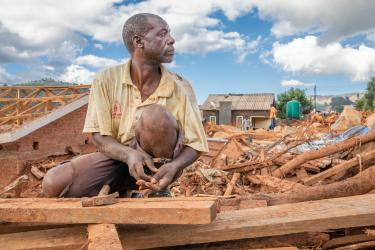 Anthony sits in front of his damaged house in Zimbabwe