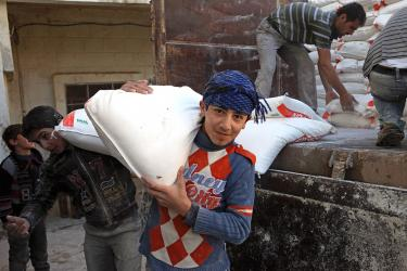 A boy carries a sack of flour over his shoulder in syria