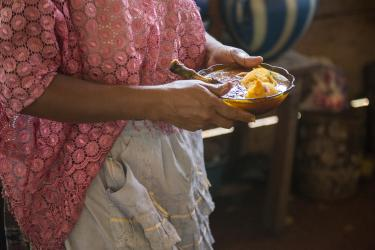 A woman carries a bowl of hearty, traditional soup in guatemala