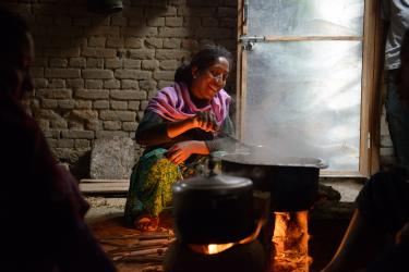 A woman cooks over a hot stove in nepal