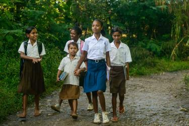 Lourdes walks to school in the company of younger classmates in Timor Leste