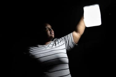 Bahamian woman holds up a solar lantern in the darkness of night.