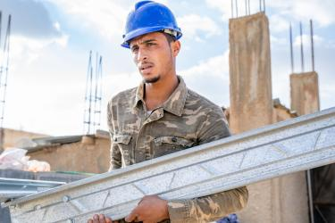 Young jordanian construction worker assembling structural building parts.