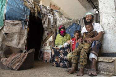 Yemeni family sitting together outside their home's entrance.