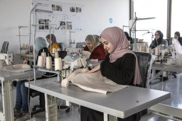 Jordanian women work in sewing company environment.