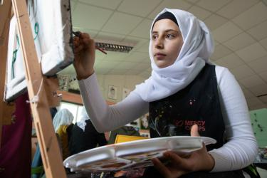 A young person paints while seated at an easel.